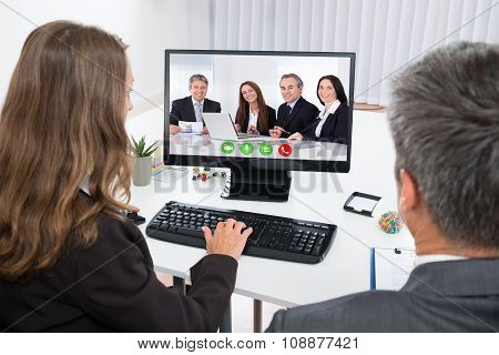 Businesspeople Video Chatting With Colleagues On Computer
