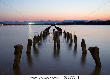 Wooden Stakes That Emerge Out Of The Lake At Colorful Sunset In Long Exposure