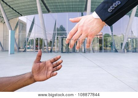 Hand Of Young American Businessman Reach Out Black Refugee Arm - Humanitarian Aid Against Racism - B