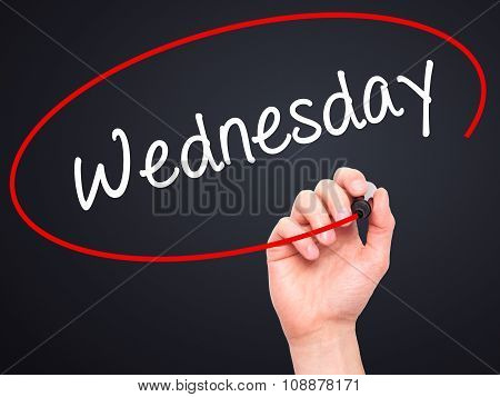 Man Hand writing Wednesday with  marker on visual screen
