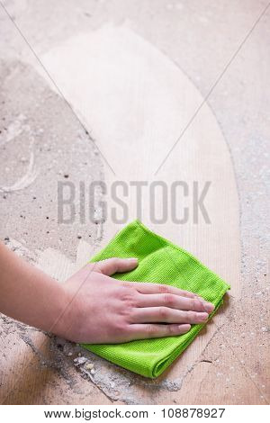 Person Cleaning Dirty Wood Floor