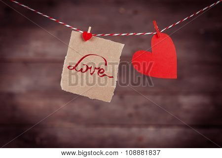 Paper hearts and sheet hanging on cord against wooden background