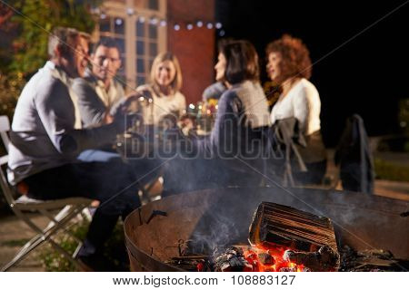 Mature Friends Enjoying Outdoor Evening Meal Around Firepit