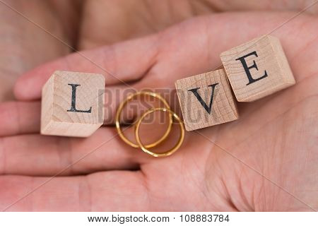 Close-up Of Hands With The Word Love