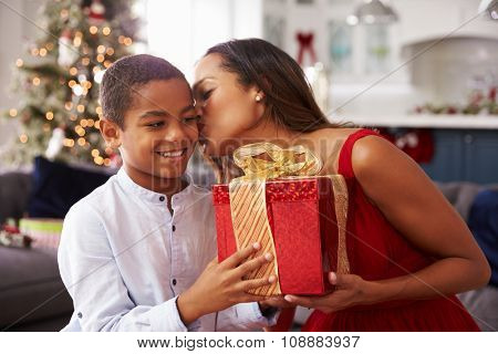 Mother Giving Christmas Presents To Son At Home