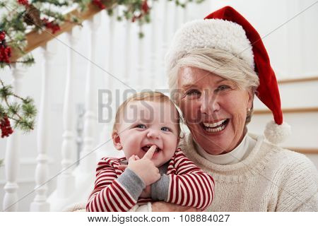Grandmother With Granddaughter Sits On Stairs At Christmas