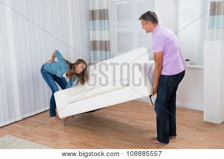 Woman Suffering From Backache While Moving Sofa