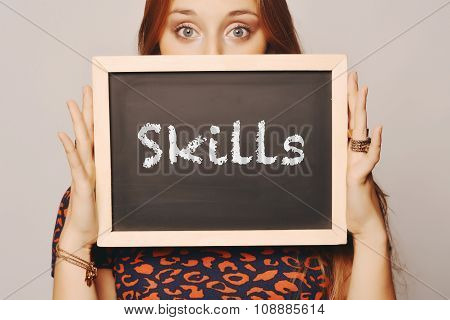 Young Woman Holding A Chalkboard Saying Skills