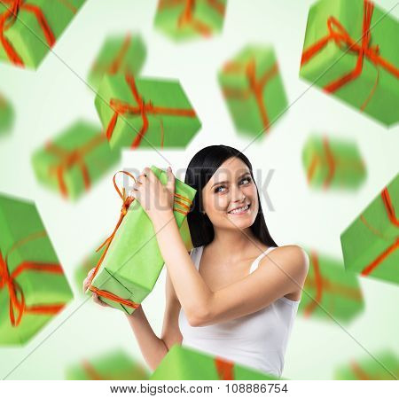 A Portrait Of Dreaming Woman Who Imagines Green Gift Boxes. Light Green Background.