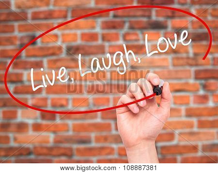 Man Hand writing Live Laugh Love with black marker on visual screen.