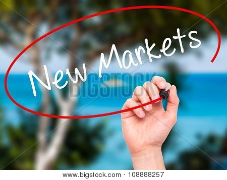 Man Hand writing New Markets with black marker on visual screen