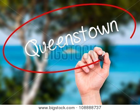 Man Hand writing Queenstown with  marker on visual screen.