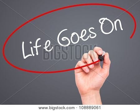 Man Hand writing Life Goes On with black marker on visual screen.