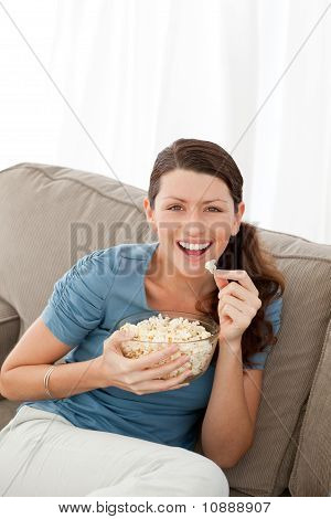 Portrait Of A Happy Woman Eating Pop Corn While Watching Television