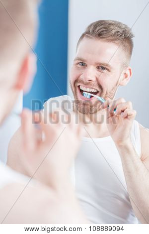 Unshaved Man Brushing His Teeth