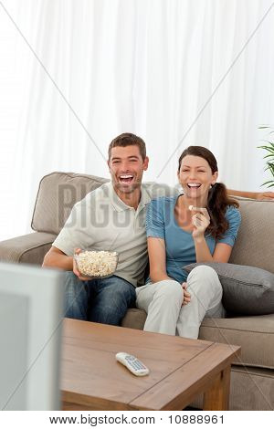 Cute Couple Eating Pop Corn While Watching Television On The Sofa