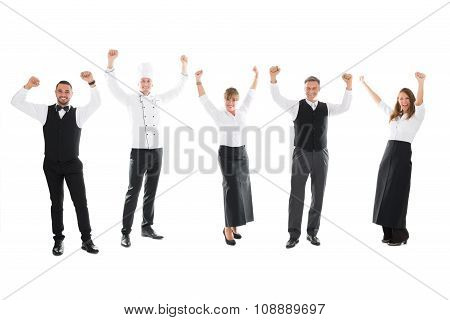 Happy Restaurant Staff Standing With Arms Raised