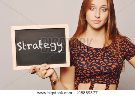 Young Woman Holding A Chalkboard Saying Strategy.