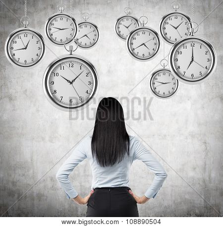 A Rear View Of A Brunette Business Lady Who Is Looking At The Hovering Pocket Watches In The Air. A