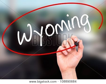 Man Hand writing Wyoming with  marker on visual screen.