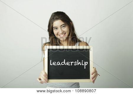 Young Woman Holding A Chalkboard Saying Leadership.