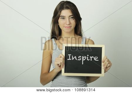 Young Woman Holding A Chalkboard Saying Inspire.