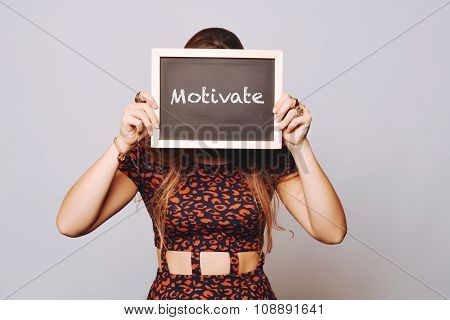Young Woman Holding A Chalkboard Saying Motivate