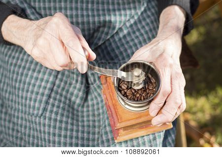 Old Hands Grinding Coffee On A Vintage Coffee Grinder