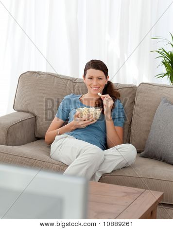 Happy Woman Eating Pop Corn While Watching Television On The Sofa