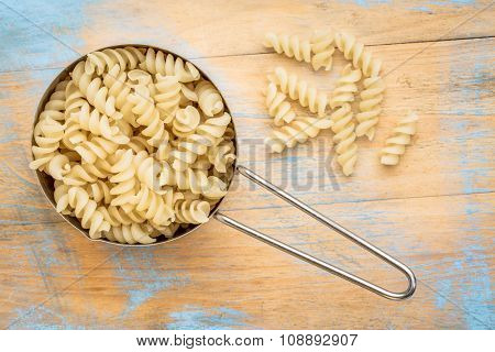 healthy, gluten free quinoa pasta (fusilli)  - top view of a metal measuring cup against painted wood