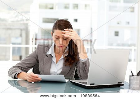 Pensive Businesswoman Looking At A Paper While Working On Her Laptop