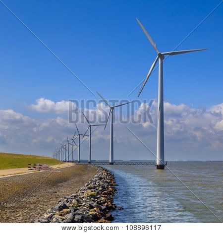 Row Of Wind Turbines Along A Breakwater