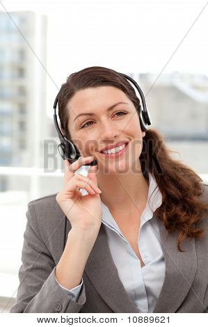 Cheerful Businesswoman Using Earpiece Sitting At Her Desk