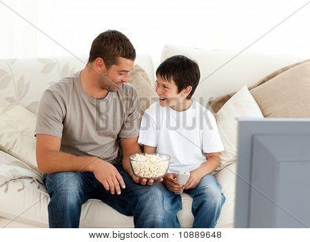 Padre e hijo viendo la televisión mientras se come palomitas de maíz en el sofá