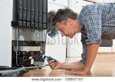 Handyman Checking Refrigerator With Flashlight At Home