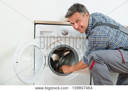 Repairman Checking Washing Machine At Home