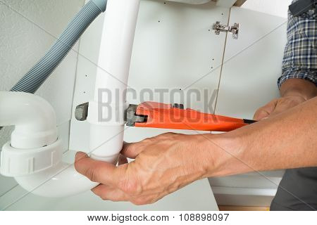 Serviceman Fixing Sink Pipe In Kitchen
