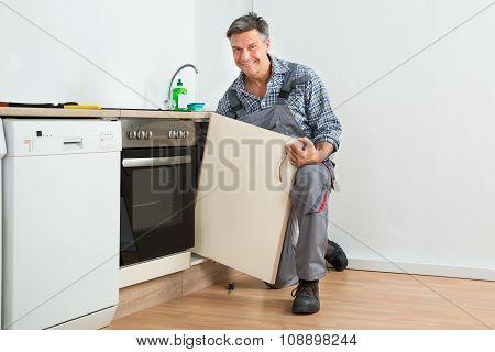 Handyman Fixing Sink Door In Kitchen