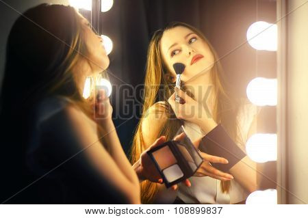 Young woman looking into a mirror at herself and use cosmetic brush