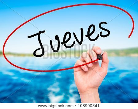 Man Hand writing Jueves (Thursday in Spanish) with black marker on visual screen.