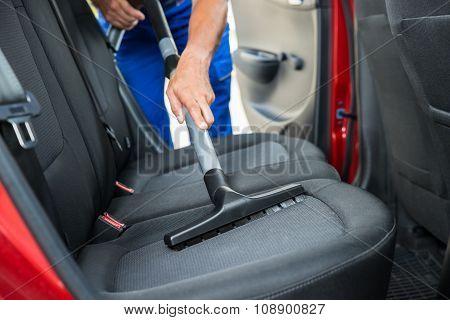 Handyman Vacuuming Car Back Seat