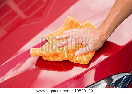 Male Worker Washing Red Car Hood