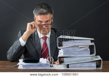 Portrait Of Businessman Checking Invoice At Desk
