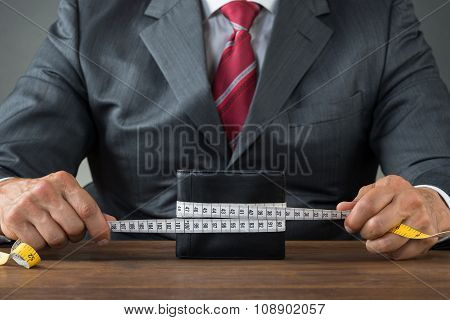 Businessman Wrapping Wallet With Measuring Tape