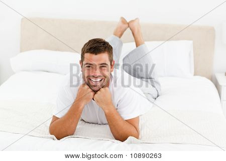 Handsome Man Laughing Lying On His Bed