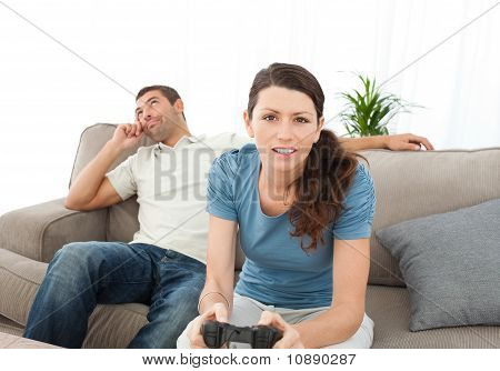 Serious Woman Playing Video Game While Her Boyfriend Waiting For Her On The Sofa
