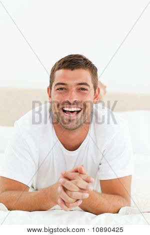 Portrait Of A Cheerful Man Relaxing In His Bedroom