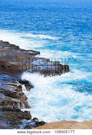 Beautiful Blue Ocean Water Hitting Against Rocky Edge