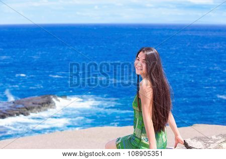 Beautiful Teen Girl Sitting On Rocky Ledge Over Blue Ocean