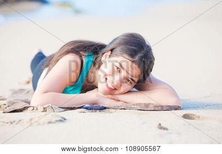 Biracial Teen Girl Lying On Sandy Beach, Resting And Smiling